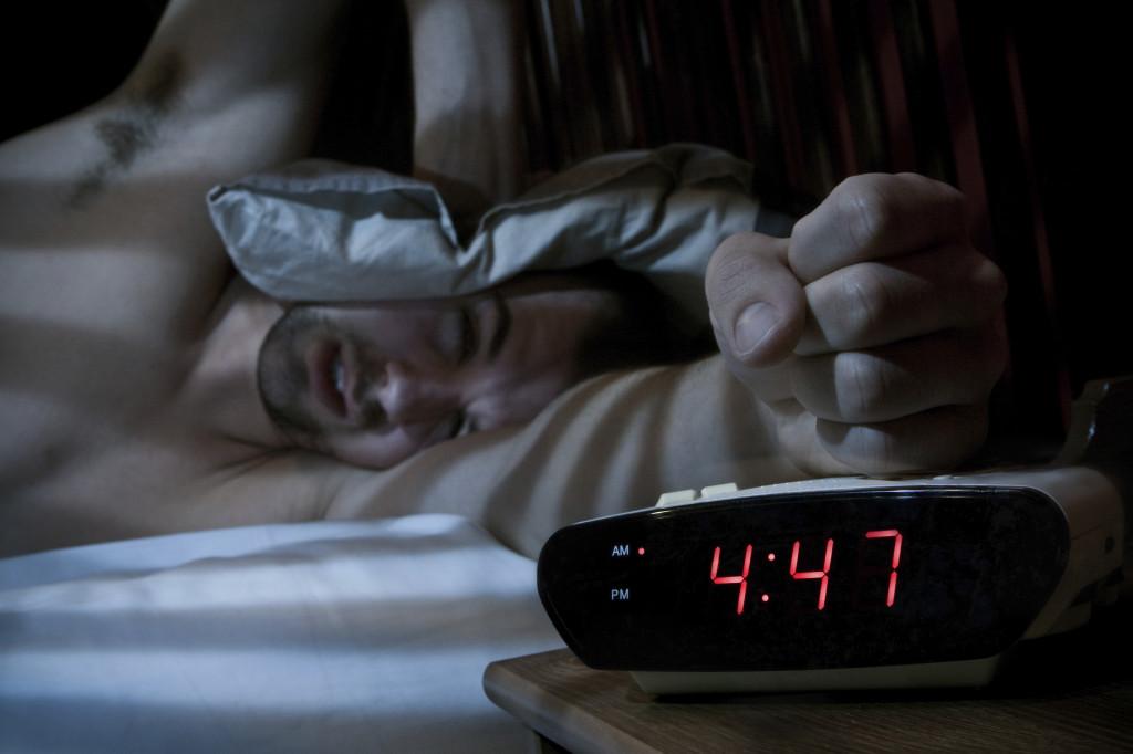 Unhappy man smashing the alarm clock.