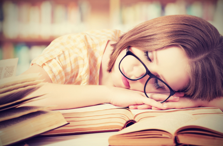 Tired student girl with glasses sleeping on books in library