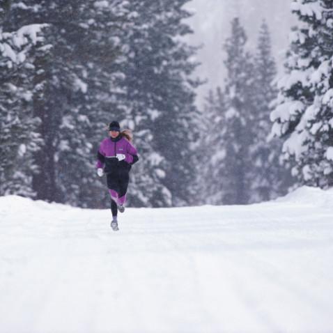 Woman jogging along road in winter