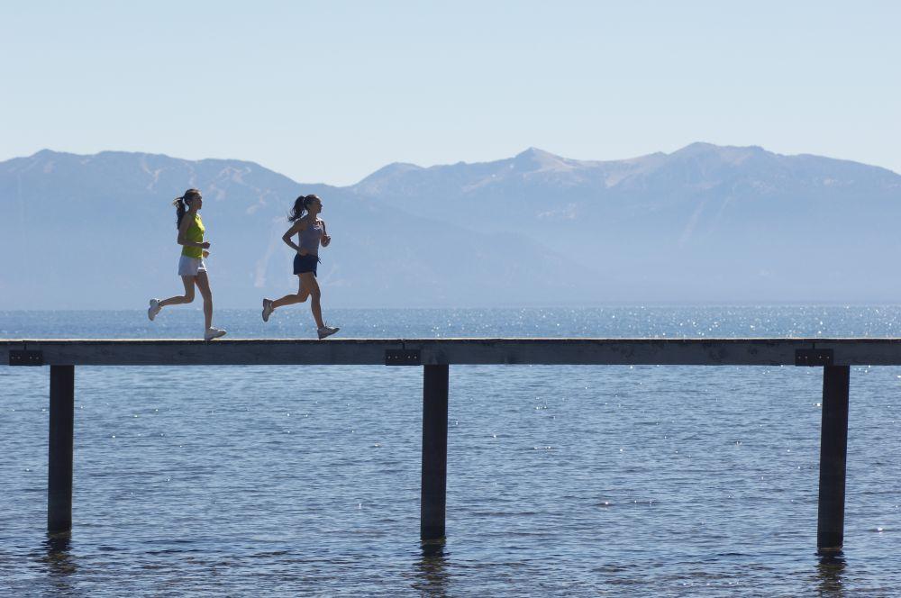 Women Jogging on Pier above Scenic Lake