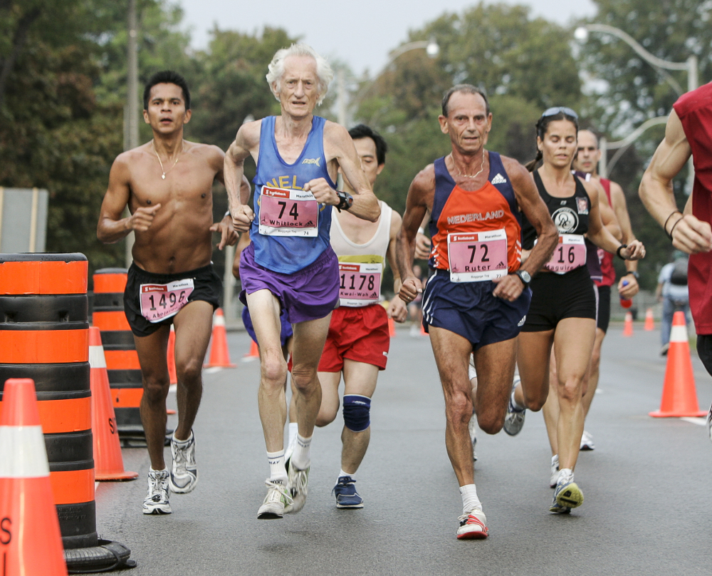 Whitlock with challenger Joop Ruter from the Netherlands, both competing in the M70–74 age group at the 2005 Toronto Waterfront Marathon, their ages reflected in their bib numbers. Whitlock outruns Ruter by 42:33 to finish in 3:02:41. Photo: Canada Running Series.