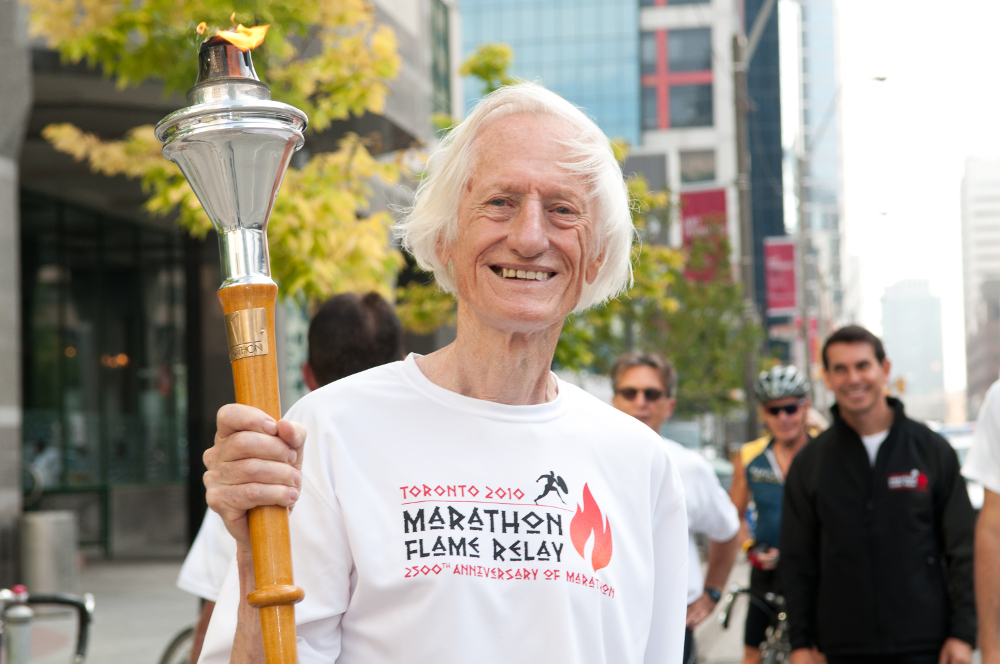 In 2010, Ed Whitlock carries the Marathon Flame through the streets of downtown Toronto, to mark the 2,500th Anniversary of the Marathon. Photo: Todd Fraser / Canada Running Series.