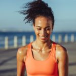 Smiling young female runner taking a breather. Healthy young woman with sweat standing on the promenade after her workout and smiling.
