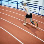 Young sportsman with prosthesis instead of right leg running down race track on stadium during competition